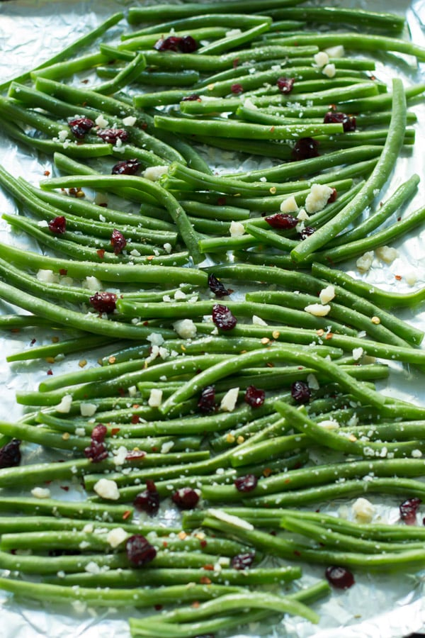 Roasted Parmesan Green Beans-Super crispy Roasted Parmesan Green Beans, topped with dried cranberries, walnuts and shredded parmesan cheese. This is definitely the easiest recipe to make a delicious and flavourful veggie side dish!