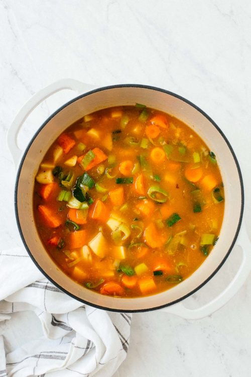 A dutch oven with vegetable soup inside.