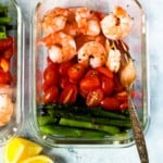 A glass meal prep container with shrimp, cherry tomatoes, and asparagus.