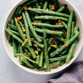 Bowl of green beans with garlic and butter.