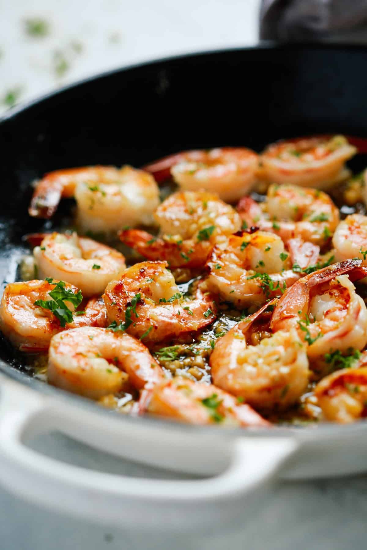 shrimp recipe being cooked in a skillet with butter and garlic seasoning