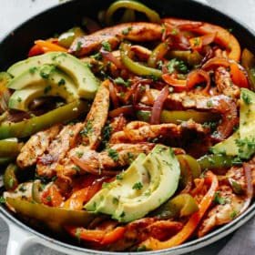 chicken fajitas topped with avocado slices