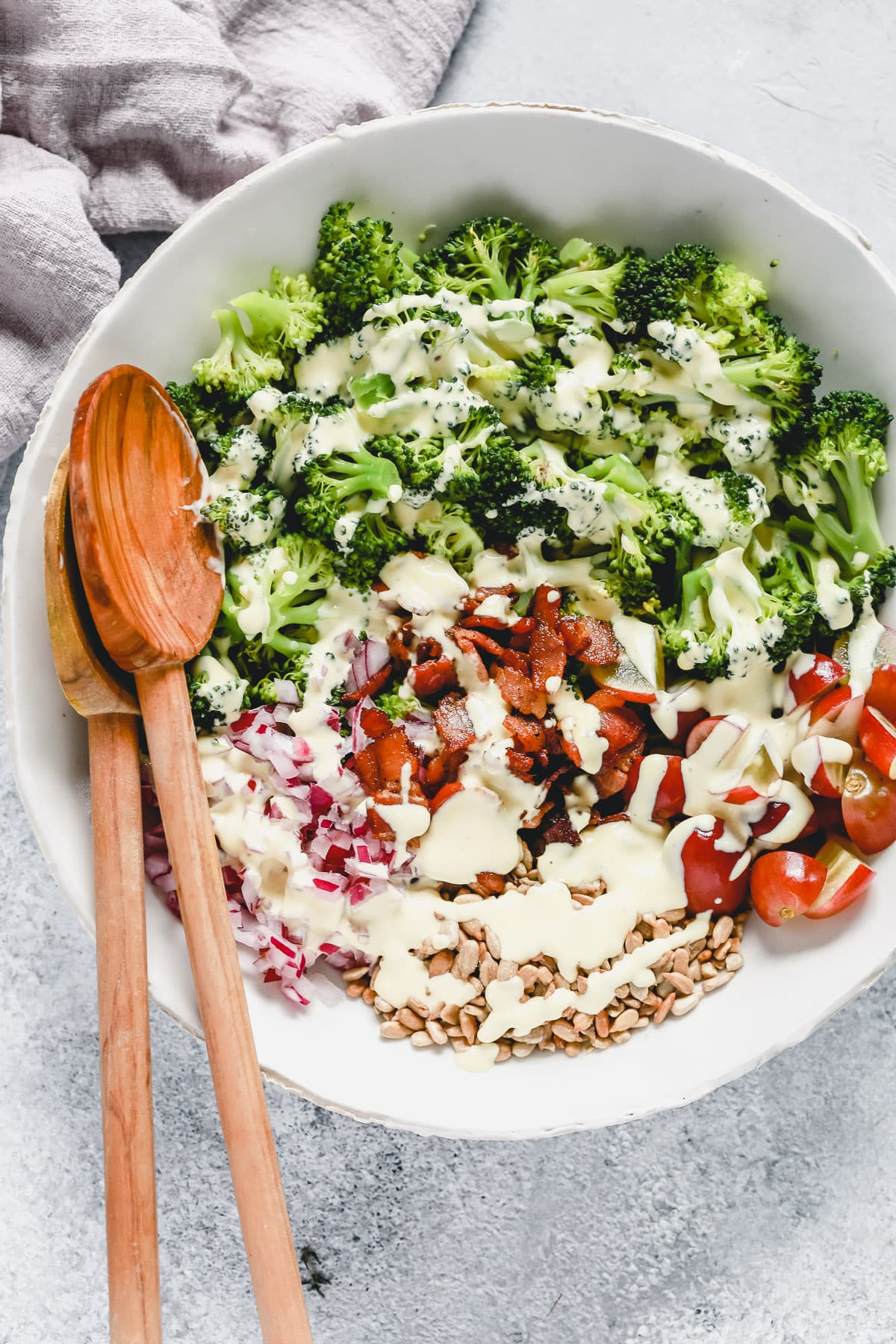 salad in white bowl with broccoli, tomatoes, bacon, onion, sesame seeds and dressing