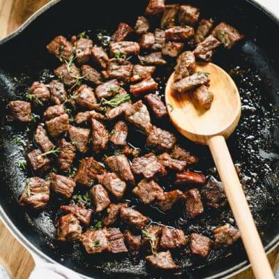 steak bites cooking in a skillet