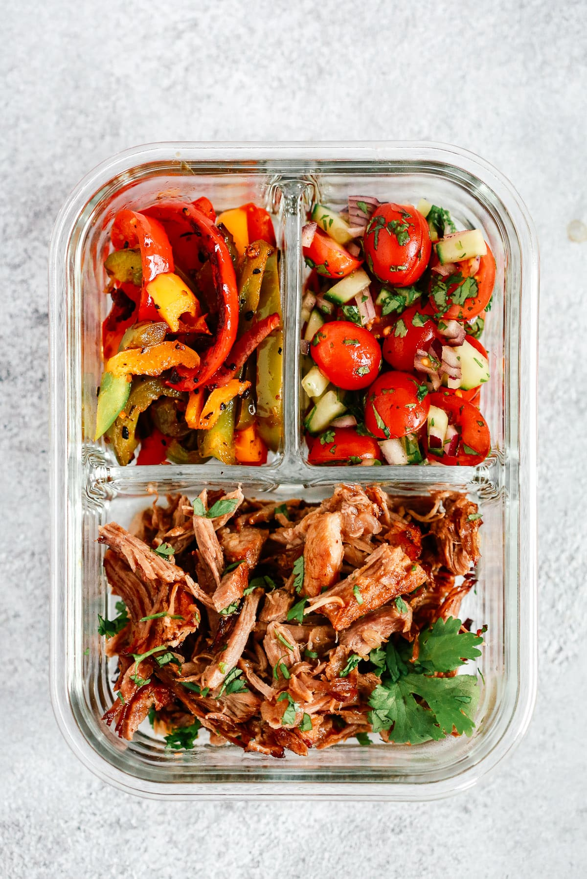 meal prep container with Mexican pulled pork, sauteed peppers and tomato salsa