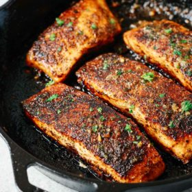 four blackened salmon fillets in a cast iron skillet
