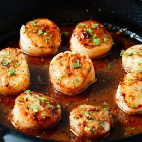 golden pan seared garlic butter scallops in a cast iron