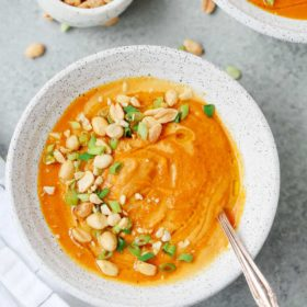 A bowl of carrot soup with green onion and peanut garnished on top.