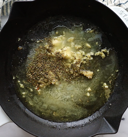 overhead view of cast iron skillet containing melted butter, garlic, lemon juice and spices.