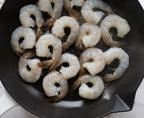 overhead view of a cast iron skillet containing raw shrimp