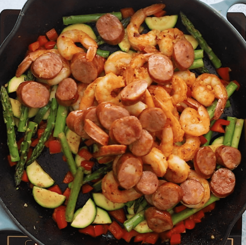 overhead view of a cast iron skillet containing shrimp and sausage