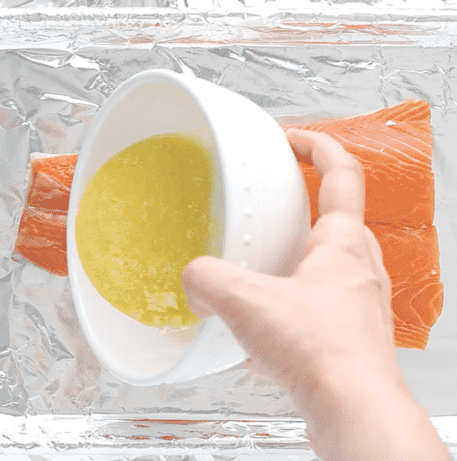 overhead view of melted butter being poured over salmon