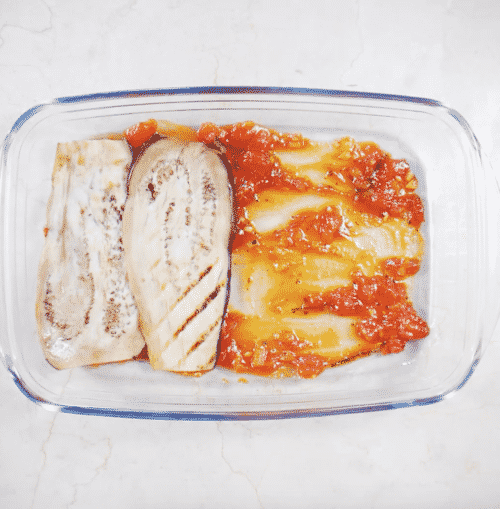 overhead view of casserole containing tomato sauce and slices of eggplant