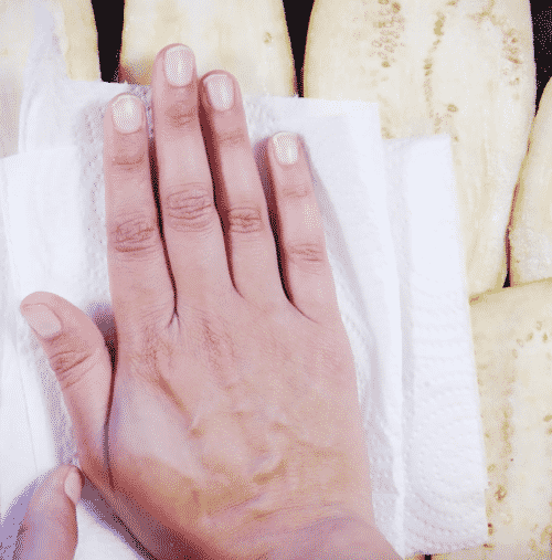 a hand removing the excess moisture and salt with a paper towel.