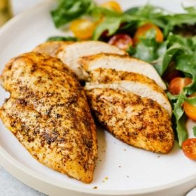 closeup of 2 air fryer chicken breast on a white plate